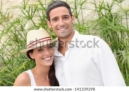 Couple in front of green branches - stock photo