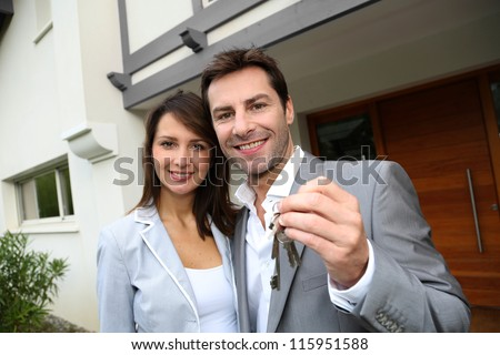 Couple in front of new home holding door keys - stock photo