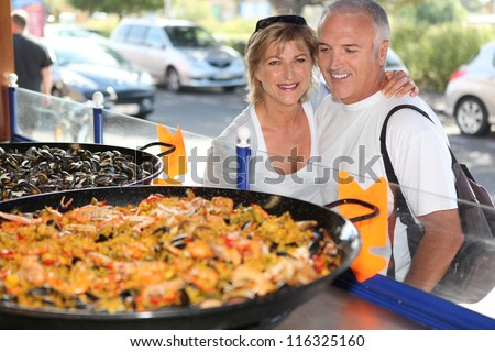 Couple in front of paella - stock photo