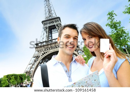 Couple in front of the Eiffel tower holding tourist pass