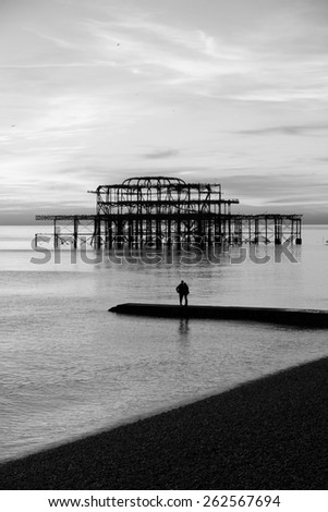 Couple in front of the remains of Brighton Pier left standing in sea at sunset, Brighton West Pier, England, UK - stock photo