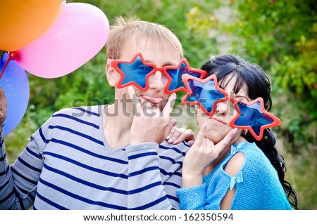 Couple in funny glasses with balloons outdoors  - stock photo