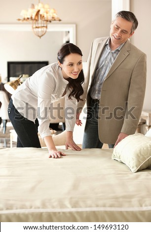 Couple in furniture store. Cheerful middle-aged couple choosing furniture in store - stock photo
