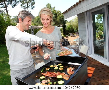 Couple in garden cooking meat on barbecue - stock photo