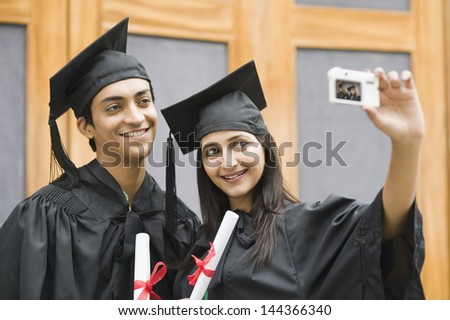 Couple in graduation gown taking a picture of themselves - stock photo