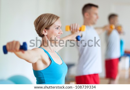Couple in gym exercising with dumbbells - stock photo