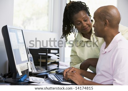 Couple in home office using computer - stock photo