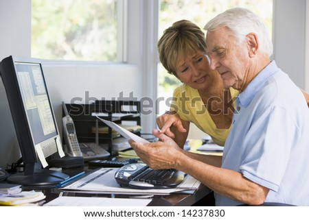 Couple in home office with computer and paperwork - stock photo