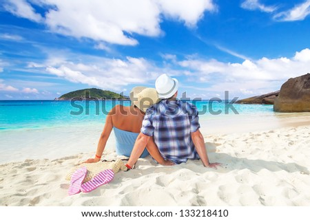 Couple in hug sitting together at the Caribbean Sea - stock photo