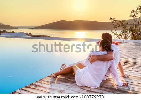 Couple in hug watching sunrise together in Greece - stock photo