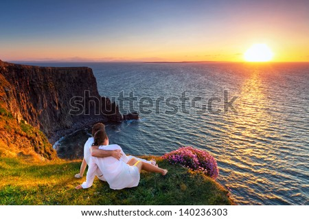 Couple in hug watching sunset on the edge of the cliff.