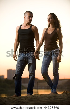 Couple in jeans on a sunset - stock photo