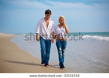 Couple in jeans walking on a beach. - stock photo