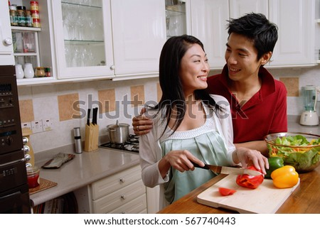 Couple in kitchen, smiling at each other, woman chopping vegetables
