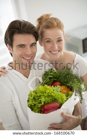 couple in kitchen with a vegetables's bag in arms