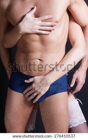Couple In Lingerie standing sideways to camera caressing man