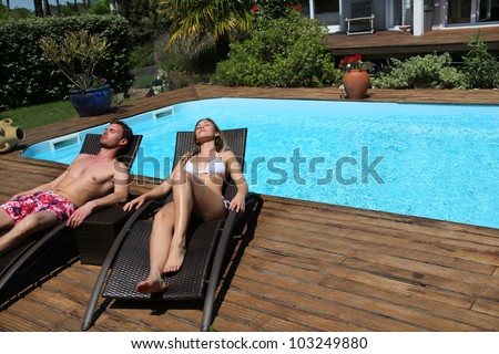 Couple in long chairs by swimming pool - stock photo