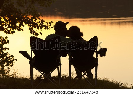 Couple in love back light silhouette at lake sunset  - stock photo