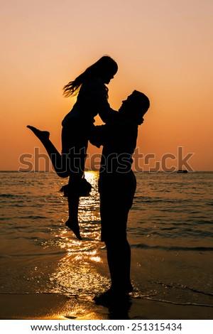Couple in love back light silhouette at sea orange sunset - stock photo