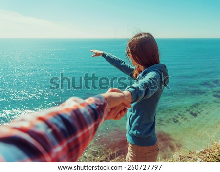 Couple in love. Beautiful young woman holding man's hand and showing him something in distance the sea. Point of view shot
