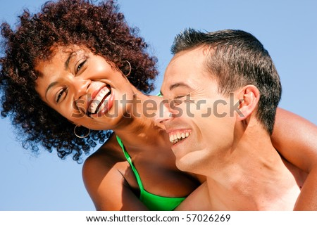 Couple in love - bikini-clad woman of color hugs a Caucasian man from behind under clear blue sky, both in beachwear in summer - stock photo