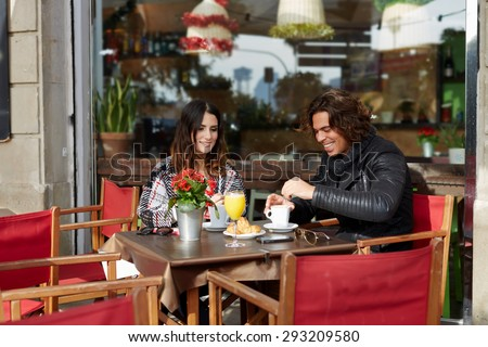 Couple in love breakfast with warm coffee and delicious dessert in sidewalk cafe at cold autumn day, two good friends met by chance are an interesting and pleasant conversation smiling at the lunch - stock photo