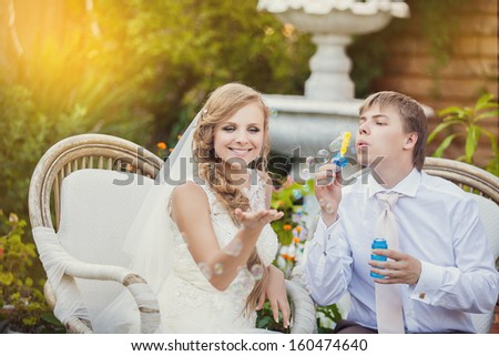 couple in love bride and groom resting on chairs with soap bubbles