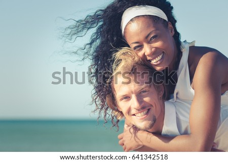 Couple in love - Caucasian man carrying his African-American woman with hands on a beach in vacation