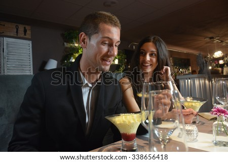 couple in love dining at an elegant restaurant and eating a tempting dessert