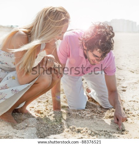 Couple in love drawing a heart in the sand while relaxing at beach - stock photo