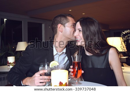 couple in love drinking cocktails in an elegant bar at night - stock photo