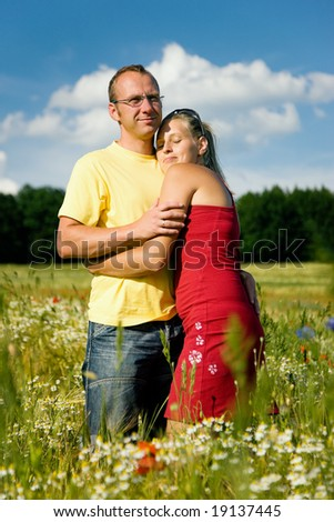 Couple in love embracing each other, standing in a field with wild flowers - stock photo