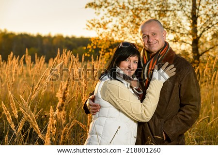 Couple in love embracing in autumn countryside backlit by sunset - stock photo