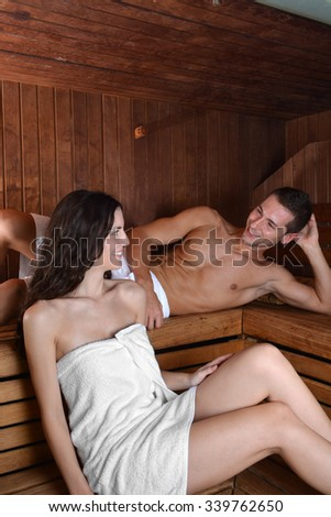 couple in love enjoying the sauna with white towels. The pleasure of a good spa session - stock photo
