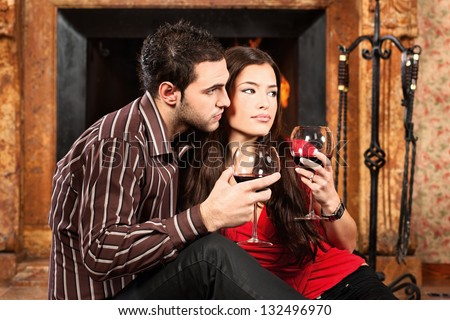 Couple in love enjoying wine near fireplace - stock photo