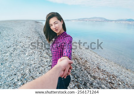Couple in love. Happy beautiful young woman holding hand her boyfriend and leading him on beach near the sea. Point of view shot - stock photo