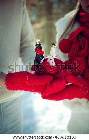 couple in love holding a chess king and queen figures in red mittens