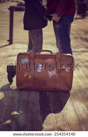 Couple in love holding hands and standing next to a suitcase - stock photo
