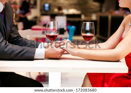 Couple in love holding hands together on table in restaurant, close up - stock photo