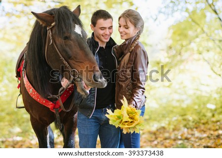 couple in love, horseback riding, tenderness, forest, fun - stock photo