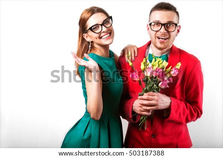 couple in love in the studio with flowers in transparent hipster glasses, the concept of Valentine's Day