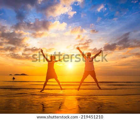 Couple in love jumping on the ocean beach during amazing sunset . Long-awaited vacation concept and romantic honeymoon. - stock photo