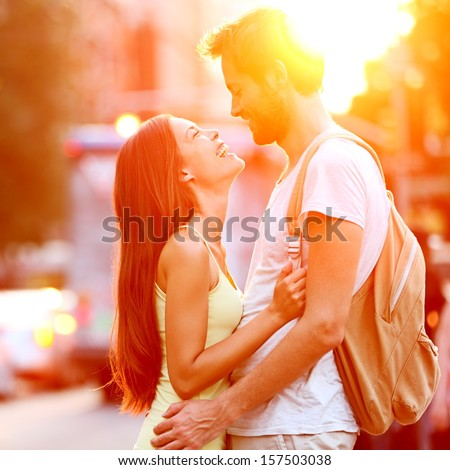 Couple in love kissing laughing having fun. Dating interracial young couple embracing on date. Caucasian man, Asian woman on Manhattan, New York City, USA.