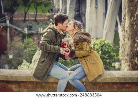 couple in love kissing on street celebrating Valentines day with girl receiving heart shaped box present in city park urban background