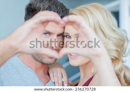Couple in Love Looking at Camera Through Hands Making Heart Shape - stock photo
