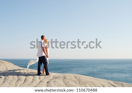 Couple in love looking at the sea holding hands - stock photo