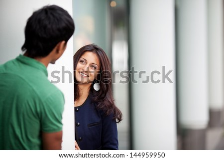 Couple in love looking from behind columns - stock photo