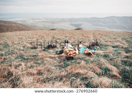 Couple in love lying on a mountain meadow above the sea in summer. Image with instagram filter - stock photo