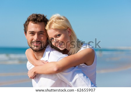Couple in love - man having his woman piggyback on his back under a blue sky on a beach - stock photo