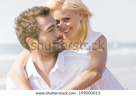 Couple in love - man having his woman piggyback on his back under a blue sky on beach